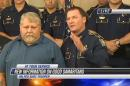 In this frame from video provided by KPLC, state police chief Mike Edmonson, right, stands with Robert Ledoux, the good Samaritan who helped capture a man accused of shooting a state trooper, Monday, Aug. 24, 2015, in Lake Charles, La. Kevin Daigle is accused of shooting Senior Trooper Steven Vincent on Sunday evening when Vincent found Daigle's truck in a ditch. (KPLC via AP) MANDATORY CREDIT; LOCAL MEDIA OUT; AMERICAN PRESS OUT