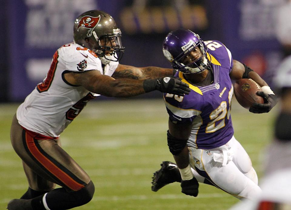 Minnesota Vikings running back Adrian Peterson, right, runs from Tampa Bay Buccaneers middle linebacker Mason Foster during the first half of an NFL football game Thursday, Oct. 25, 2012, in Minneapolis. (AP Photo/Andy King)