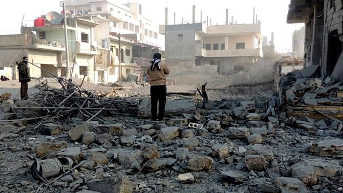 This citizen journalism image provided by Edlib News Network, ENN, which has been authenticated based on its contents and other AP reporting, two Syrian rebels inspect the rubble of damaged buildings due to government airstrikes, in Bensh, Idlib Province, northern Syria, Tuesday, Jan. 15, 2013. (AP Photo/Edlib News Network ENN)