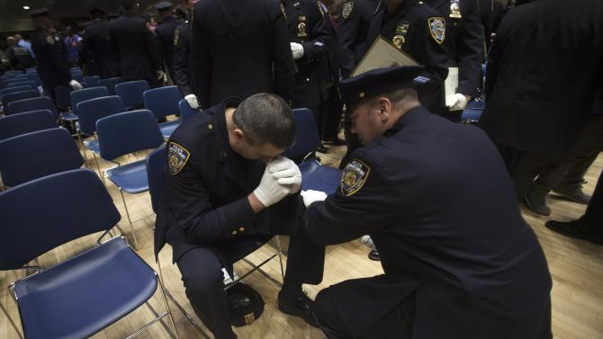 A policeman takes a moment to gather himself as another officer puts his hand on his knee following a New York Police Department Promotion Ceremony at Police Headquarters in the Manhattan borough of New York