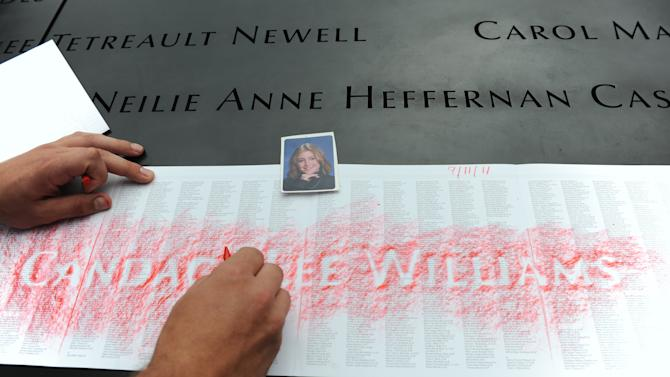FILE - In this Sept. 11, 2011 file photo,  Corey Gaugioso makes a rubbing of the name of his sister, Candace Lee Williams, on a wall surrounding the reflecting pool at the National September 11 Memorial in New York on the 10th anniversary of the attacks on the World Trade Center. The memorial, which includes a bronze parapet outlining the footprints of the twin towers and engraved with the names of those killed in the attacks, was designed with the rubbings in mind. Williams was on Flight 11, which crashed into the same tower where she worked for Merrill Lynch. (AP Photo/David Handschuh, File)