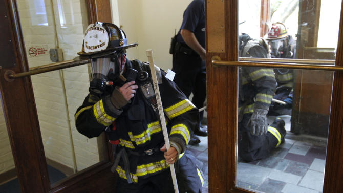 Worcester firefighter Lt. Jeffery Dubeau, front, enters a building with other firefighters, right, on the campus of Worcester Polytechnic Institute, in Worcester, Mass., during a test exercise for safety tracking devices, in Worcester, Mass., Tuesday, Aug. 2, 2011. As the ten year anniversary of the Sept. 11 attacks approaches, researchers, fire fighters, and government officials are working to perfect technology that tracks the location and vital signs of first responders. (AP Photo/Steven Senne)