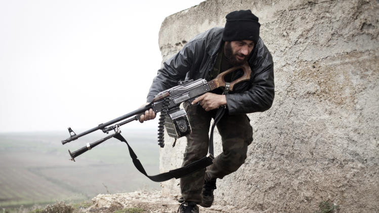 In this Monday, Dec. 17, 2012 photo, a Free Syrian Army fighter takes cover during fighting with the Syrian Army in Azaz, Syria. (AP Photo/Virginie Nguyen Huang)