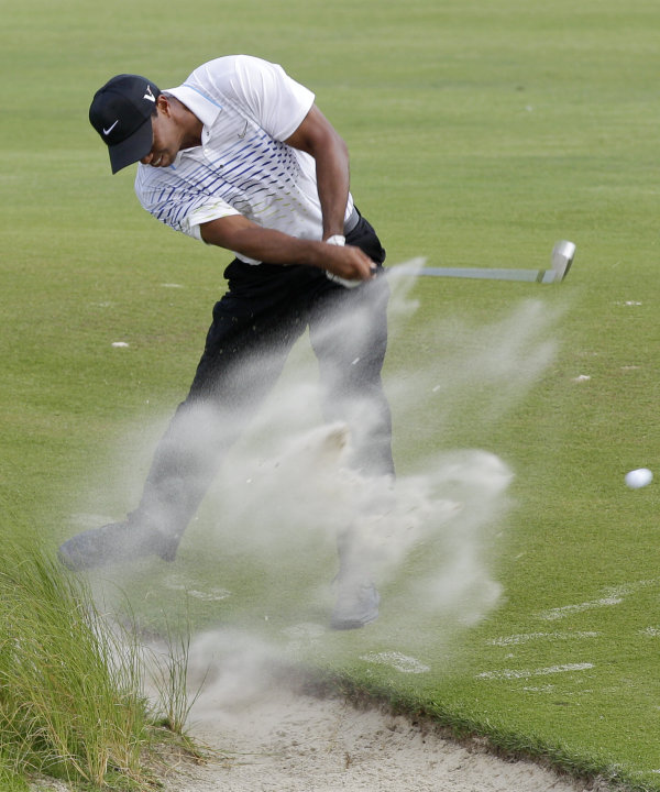 Tiger Woods hits from the sand along the seventh fairway during the third round of the PGA Championship golf tournament on the Ocean Course of the Kiawah Island Golf Resort in Kiawah Island, S.C., Sat