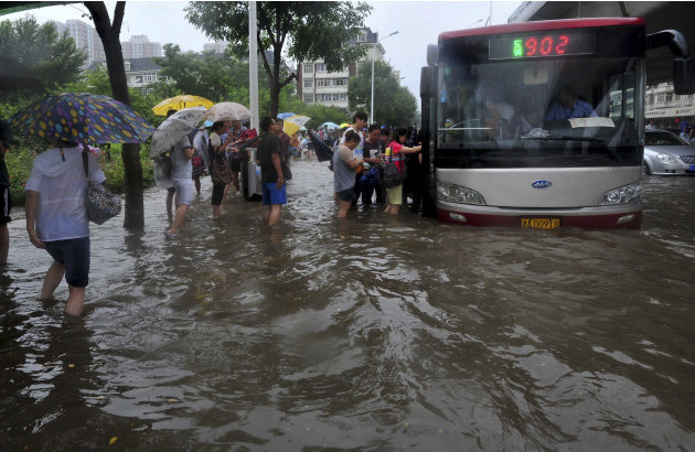 Commuters try to get on a bus on a flooded road following a heavy rain, in Tianjin, China Thursday, July 26, 2012. Residents impatient for official updates compiled their own death tolls Thursday for