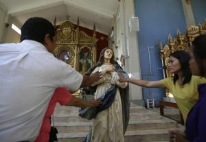 Typhoon survivors touch an image of Mary inside the …