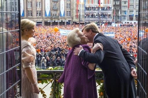 The Netherlands King Willem Alexander (R) kissing his mother Queen Beatrix while his wife Maxima watches on a balcony of the Royal Palace in Amsterdam. The Netherlands' Willem-Alexander became Europe'