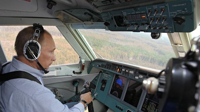 FILE- In this Tuesday, Aug. 10, 2010 file photo, then Russian Prime Minister Vladimir Putin sits in the co-pilot's seat in the cockpit of an Emergencies Ministry's Beriev Be-200 amphibian multirole jet,  flying drop water over forest fires in Ryazan region, some 180 km (111 miles) southeast of Moscow.  Vladimir Putin turns 60-years old on Sunday, Oct. 7, 2012, and has recently sought to demonstrate his youthful vigor by many personal endeavors, but while he has shown creativity in his action-man stunts, the Russian president seems surprisingly vulnerable to the vagaries of oil prices. (AP Photo/RIA Novosti, Alexei Nikolsky,file)