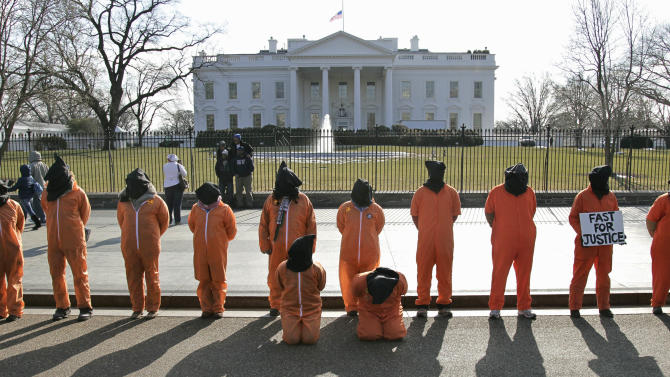 FILE - In this Jan. 14, 2011, file photo human rights activists, hooded and wearing orange prison garb to represent prisoners at Guantanamo Bay, Cuba, demonstrate in front of the White House in Washington because the prison has not been closed down by President Obama. Guantanamo Bay detainee Musa'ab Omar A Madhwani says in a federal court declaration he feels abandoned by President Barack Obama and the world after more than 10 years at the U.S. prison. (AP Photo/J. Scott Applewhite, File)