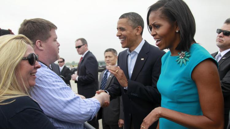 President Barack Obama and first lady Michelle Obama greet people who gathered for their arrival at Rickenbacker International Airport Saturday, May 5, 2012 in Columbus, Ohio. (AP Photo/Haraz N. Ghanbari)