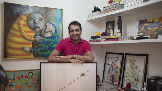 """In this Aug.  21, 2012 photo, Beto Silva, who works as a salesman at a luxury clothing store, poses for a photo with his art piece by artist Waltercio Caldas, titled """"Fim Fim,""""' or """"End End,"""" inside his apartment in Rio de Janeiro, Brazil. Like other thriving middle-class Brazilians, Silva has bought his way into the growing ranks of collectors who are helping to put Rio de Janeiro on the international art map.  (AP Photo/Felipe Dana)"""