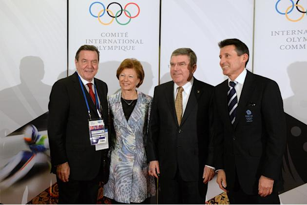 International Olympic Committee President Thomas Bach, second from right, and his wife Claudia, second from left, pose with former German Chancellor Gerhard Schroeder, left, and former British athlete