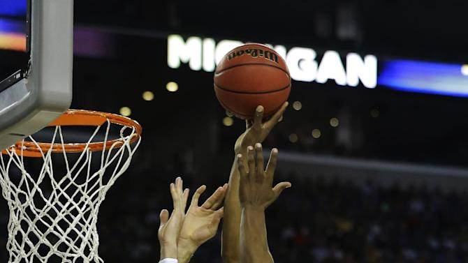 Michigan's Glenn Robinson III shoots over Kansas' Jeff Withey during the first half of a regional semifinal game in the NCAA college basketball tournament, Friday, March 29, 2013, in Arlington, Texas. (AP Photo/Tony Gutierrez)