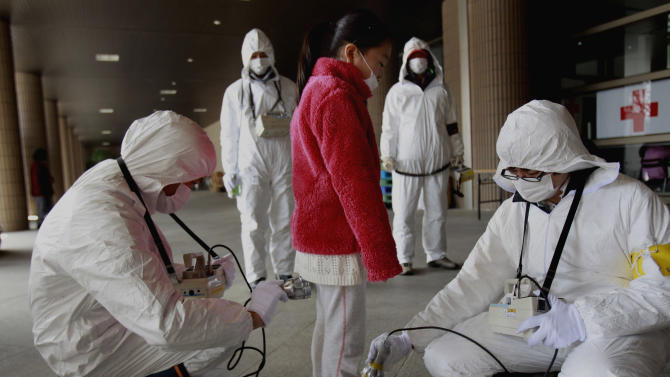 FILE - In this March 24, 2011 file photo, a young evacuee is screened at a shelter for leaked radiation from the damaged Fukushima nuclear plant in Fukushima, Fukushima prefecture, Japan. Influential Japanese scientists who help set national radiation exposure limits have for years had trips paid for by the country's nuclear plant operators to attend overseas meetings of the world's top academic group on radiation safety. Some of these same scientists have consistently given optimistic assessments about the health risks of radiation, interviews with the scientists and government documents show. Their pivotal role in setting policy after the March 2011 tsunami and ensuing nuclear meltdowns meant the difference between schoolchildren playing outside or indoors and families staying or evacuating. (AP Photo/Wally Santana, File)