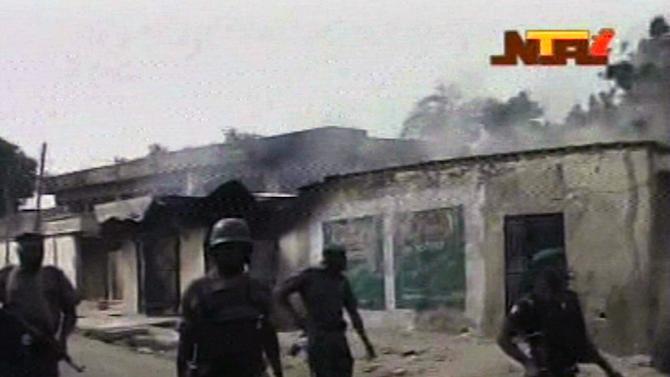 In this frame grab from TV footage shot by the Nigeria television authority on Monday, Oct. 8, 2012, but aired Tuesday, Oct. 9, 2012, soldiers walk past  burnt out houses in Maiduguri  , Nigeria. Nigerian officials dumped dozens of corpses in front of a hospital in northeast Nigeria after soldiers opened fire and killed more than 30 civilians. The hospital, overwhelmed by the scale of the violence, had to turn away the dead as its morgue had no more room. The killings Monday come as besieged, underpaid and enraged soldiers remain targets of guerrilla attacks by the extremist Islamist sect, Boko Haram, which holds this city in the grip of bloody violence.  (AP Photo / Nigeria Television Authority)