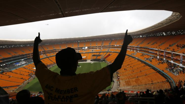 People arrive at the FNB Stadium ahead of the national memorial service for late former South African President Mandela in Johannesburg