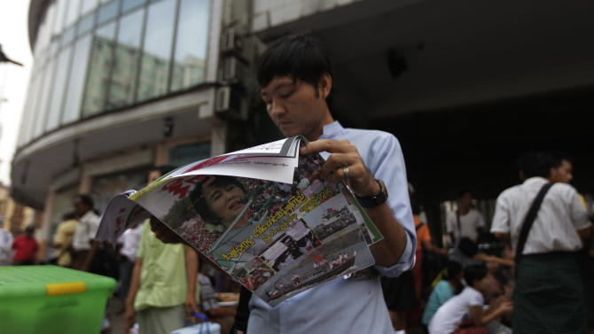 A Myanmar man reads a newspaper featuring pro-democracy leader Aung San Suu Kyi, a day after landmark by-elections in Yangon, Myanmar, Monday, April 2, 2012. Suu Kyi, 66, was elected to parliament Sunday in a historic victory buffeted by the jubilant cheers of supporters who hope her triumph will mark a major turning point in a nation still emerging from a ruthless era of military rule. (AP Photo/Altaf Qadri)