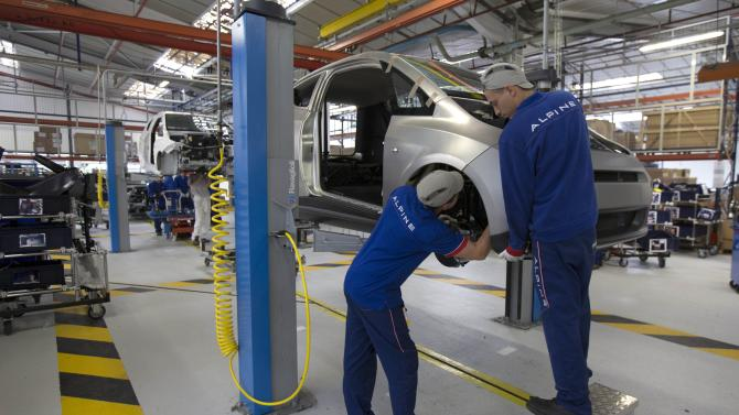 Employees work on the automobile assembly line of Bluecar electric city cars at Renault car maker factory in Dieppe, western France