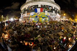 Candles and flowers are laid at the base of the Monument …