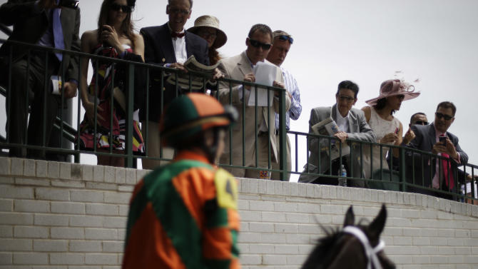 Spectators watch as Believe You Can ridden by Rosie Napravnik makes its way out to the track for the sixth race before the running of the 139th Kentucky Oaks at Churchill Downs Friday, May 3, 2013, in Louisville, Ky. (AP Photo/David Goldman)