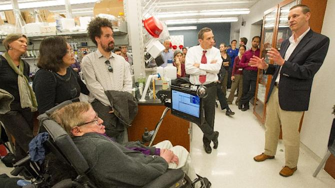 In this photo provided by Cedars-Sinai, British cosmologist Stephen Hawking, left, listens to a presentation by Robert H. Baloh, MD, PhD, the Director of Neuromuscular Medicine in the Department of Neurology, center, and Clive Svendsen, PhD, director of the Cedars-Sinai Regenerative Medicine Institute, as they give him a tour of the Regenerative Medicine Institute at Cedars-Sinai Medical Center on Tuesday, April 9, 2013 in Los Angeles. (AP Photo/Cedars-Sinai, Eric Reed)