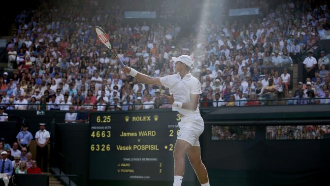 Vasek Pospisil of Canada hits a shot during his match against James Ward of Britain at the Wimbledon Tennis Championships in London