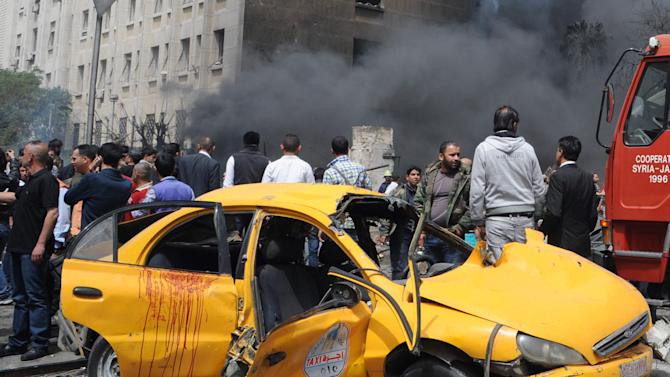 This photo provided by the Syrian official news agency SANA, shows Syrians inspecting a damaged car at the scene of a car bomb attack near the Sabaa Bahrat Square, one of the capital's biggest roundabouts, in Damascus, Syria, Monday, April. 8, 2013. The car bomb rocked a busy residential and commercial district in central Damascus on Monday, killing more than a dozen with many more injured and sending a huge cloud of black smoke billowing over the capital's skyline, Syrian state-run media said. (AP Photo/SANA)
