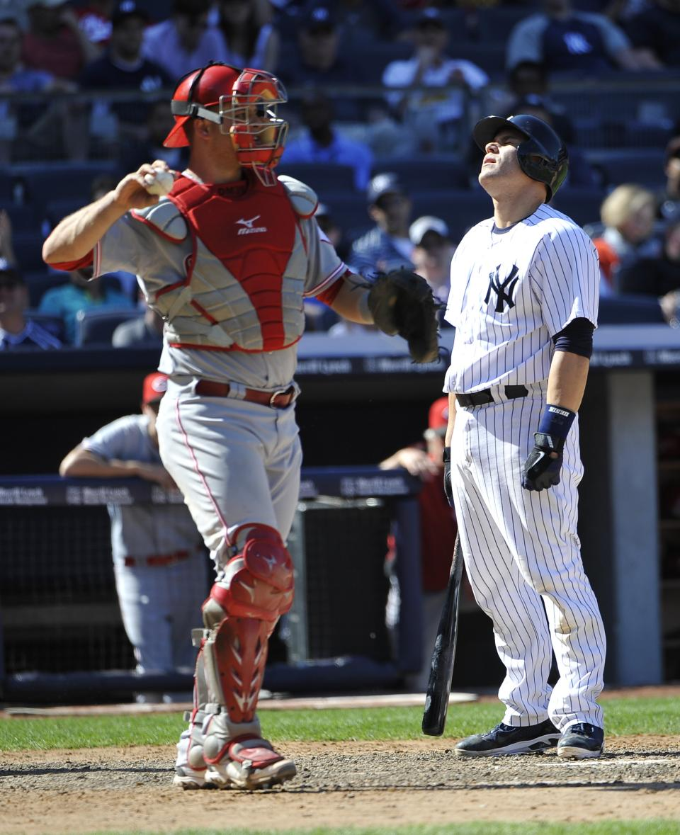 New York Yankees' Russell Martin reacts after striking out as Cincinnati Reds catcher Devin Mesoraco throws the ball back to relief pitcher Sean Marshall in the ninth inning of a baseball game on Saturday, May 19, 2012, at Yankee Stadium in New York. The Reds won 6-5. (AP Photo/Kathy Kmonicek)