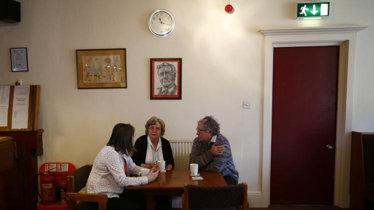 Members drink tea under a portrait of former MP Tony Benn at the Labour Club in Chesterfield