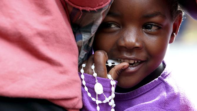 A child holds rosary beads before Pope Francis' arrival at the Kangemi slums on the outskirts of Kenya's capital Nairobi