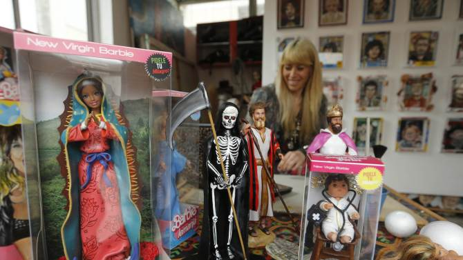 """Marianela Perelli works behind """"Barbie"""" and """"Ken"""" dolls that she and her partner Emiliano Paolini (not pictured) have re-designed into religious at their workshop in Rosario"""