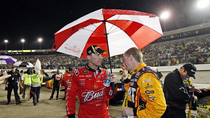 Kevin Harvick, left, talks with Jeff Burton during a rain delay for the NASCAR Sprint Cup Series auto race at Richmond International Raceway in Richmond, Va., Saturday, Sept. 8, 2012. (AP Photo/Steve Helber)