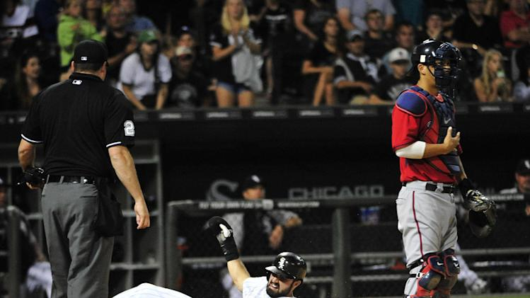 Chicago White Sox's Adam Eaton, center, scores on a single by Jose Abreu as Minnesota Twins catcher Kurt Suzuki stands nearby during the fourth inning of a baseball game, Friday, Aug. 1, 2014, in Chicago. (AP Photo/David Banks)