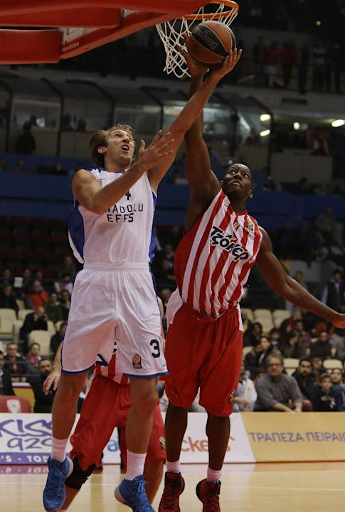 Olympiakos' Bryant Dunston, right, stops Anadolou Efes' Zoran Planinic during their Euroleague basketball match of Top 16 in the port of Piraeus, near Athens, Greece, Thursday, Feb. 13, 2014