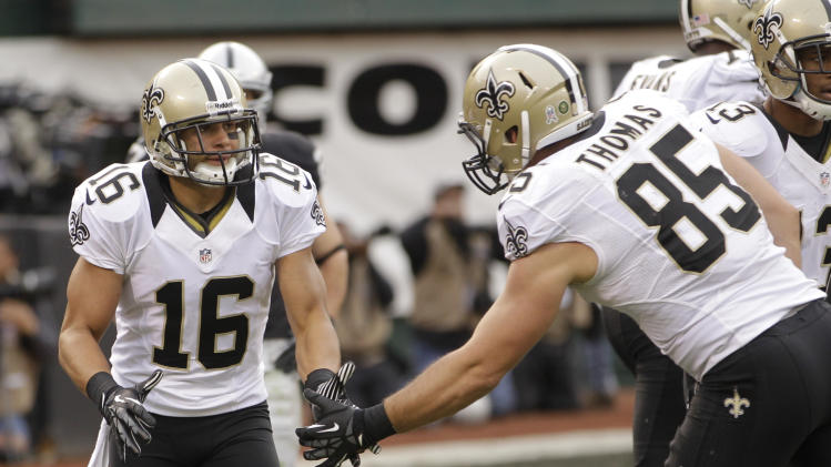 New Orleans Saints wide receiver Lance Moore, left, is greeted after scoring a touchdown after a 15-yard pass from tight end David Thomas, right, during the third quarter of an NFL football game against the Oakland Raiders in Oakland, Calif., Sunday, Nov. 18, 2012. (AP Photo/Ben Margot)