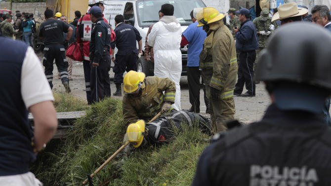 Emergency workers search for human remains in a ditch after a truck loaded with fireworks exploded during a religious procession in the town of Nativitas, Mexico, Friday, March 15, 2013. A truck loaded with fireworks exploded during a religious procession in this rural village in central Mexico, killing at least nine people and injuring dozens more, authorities said. (AP Photo/J. Guadalupe Perez)