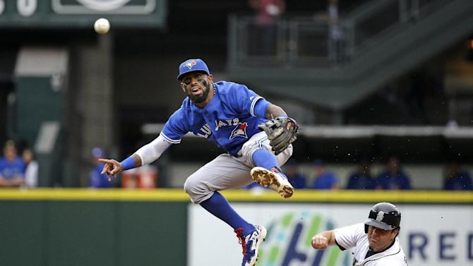 Toronto Blue Jays shortstop Jose Reyes, left, leaps out of the way after forcing out Seattle Mariners' Seth Smith at second base and throwing to first in the third inning of a baseball game Saturday, July 25, 2015, in Seattle. Logan Morrison was safe at first on the fielder's choice. (AP Photo/Elaine Thompson)