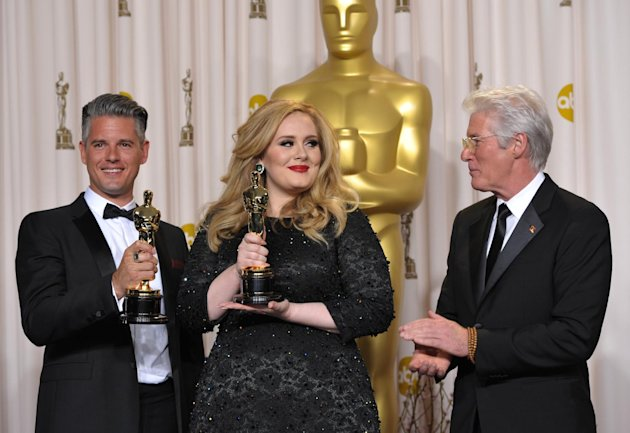 Adele and Paul Epworth pose with their award for best original song for &quot;Skyfall&quot; with presenter Richard Gere during the Oscars at the Dolby Theatre on Sunday Feb. 24, 2013, in Los Angeles. (Photo by John Shearer/Invision/AP)