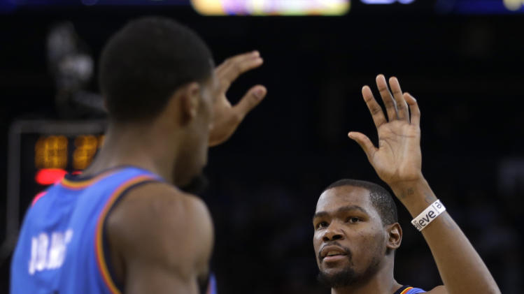 CORRECTS DATE TO JAN. 23, NOT JAN. 22 - Oklahoma City Thunder's Kevin Durant, right, celebrates with Perry Jones (3) during the first half of an NBA basketball game against the Golden State Warriors Wednesday, Jan. 23, 2013, in Oakland, Calif. (AP Photo/Ben Margot)