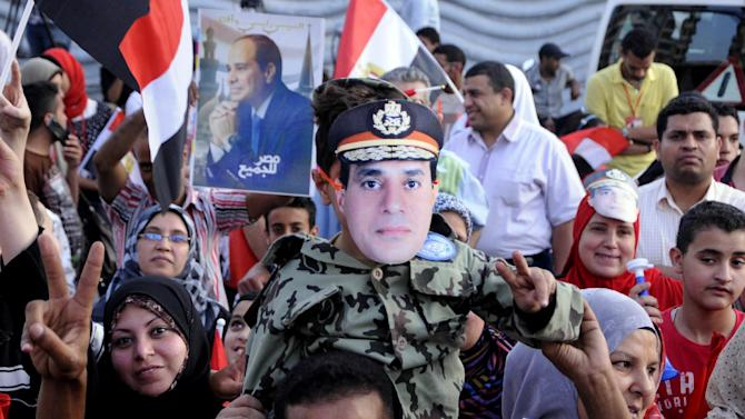 Supporters of Egypt's former military chief Abdel-Fattah el-Sissi react to the official announcement declaring him the next president of Egypt with 96.9 percent of the vote, and a turnout of 47.45 percent, in Alexandria, Egypt, Tuesday, June 3, 2014. El-Sissi's victory was never in doubt, but the career infantry officer had pushed for a massive turnout as well to bestow legitimacy on his ouster last July of Islamist President Mohammed Morsi and the ensuing crackdown on his Muslim Brotherhood and Islamist supporters. (AP Photo/Mohammed Asad)