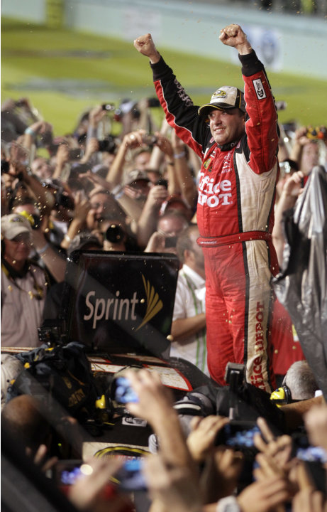Tony Stewart celebrates after winning the NASCAR Sprint Cup Series auto race and clinching the series championship, at Homestead-Miami Speedway in Homestead, Fla., Sunday, Nov. 20, 2011. (AP Photo/Chu