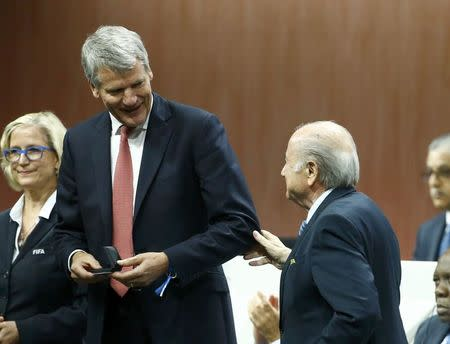 Gill of England receives his nomination at the Executive Committee from FIFA President Blatter at the 65th FIFA Congress in Zurich