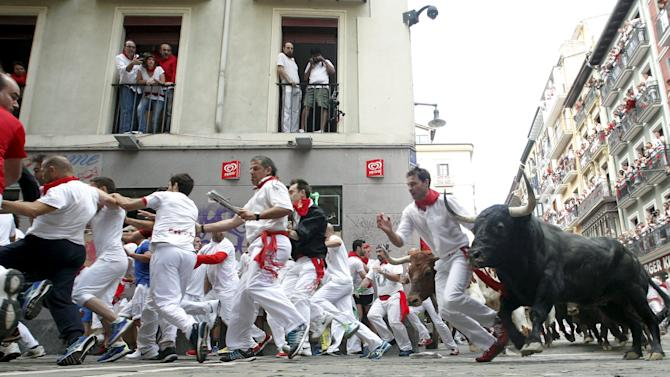 Runners lead El Tajo y La Reina ranch fighting bulls at the Mercaderes curve during the second running of the bulls of the San Fermin festival in Pamplona
