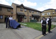 Police officers stand outside a house in Stratford east London, July 5, 2012. REUTERS/Paul Hackett