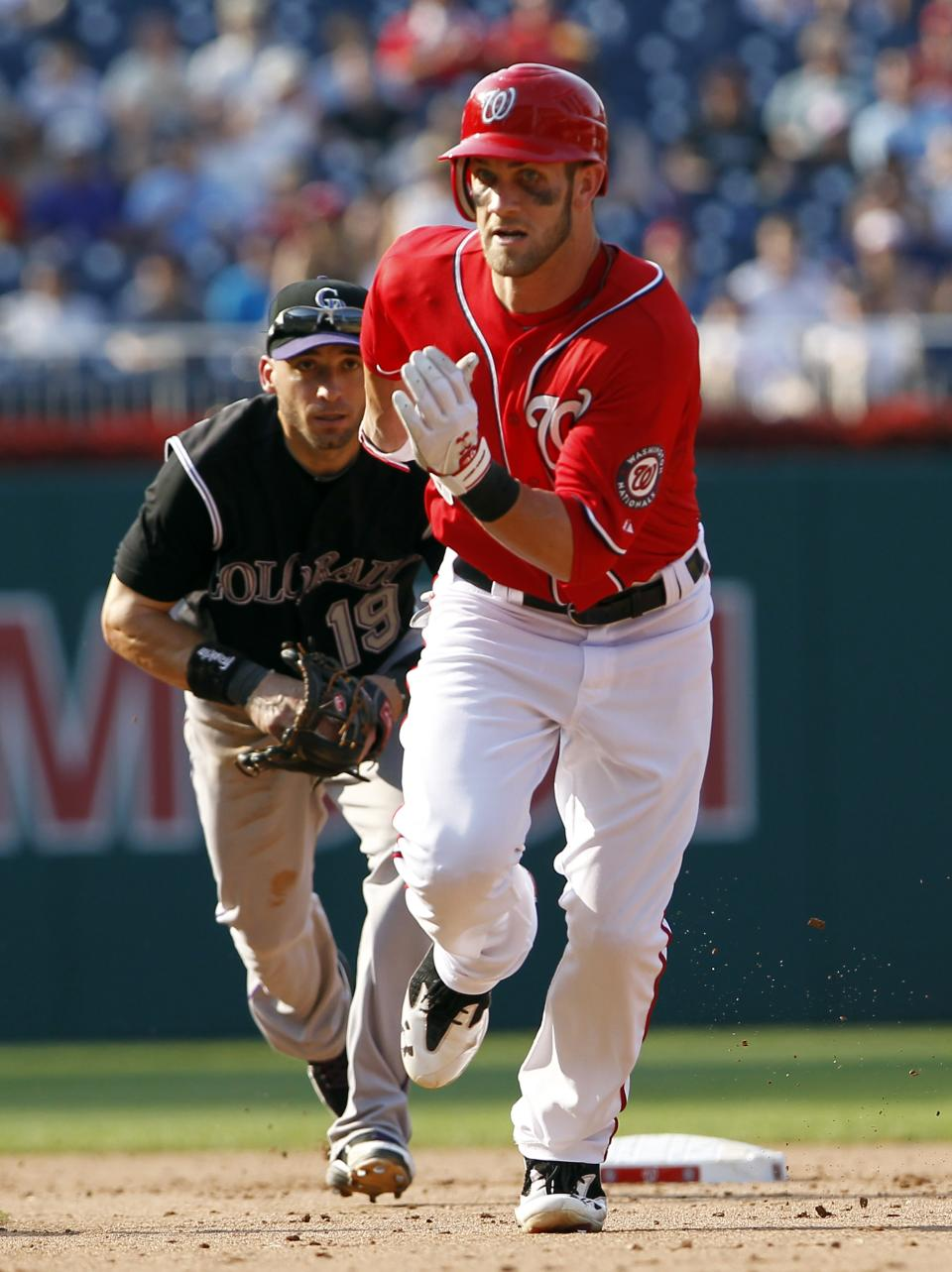 Washington Nationals' Bryce Harper is chased back to first base by Colorado Rockies second baseman Marco Scutaro (19) during the sixth inning of a baseball game Saturday, July 7, 2012 in Washington. The Nationals won 4-1. (AP Photo/Alex Brandon)