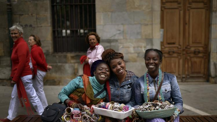 Jewellery sellers from Senegal smile during the San Fermin festival in Pamplona