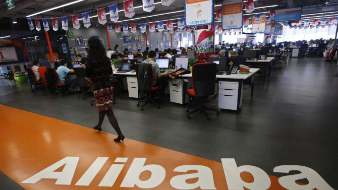 File photo of an employee walking past a logo of Alibaba Group at its headquarters on the outskirts of Hangzhou