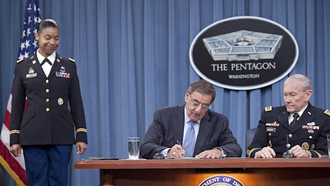 Defense Secretary Leon Panetta, flanked by Joint Chiefs Chairman Gen. Martin Dempsey, right, and Army Lt. Col. Tamatha Patterson, of Huntingdon, Tenn., signs a memorandum ending the 1994 ban on women serving in combat roles in the military, Thursday, Jan. 24, 2013, at the Pentagon. (AP Photo/Cliff Owen)