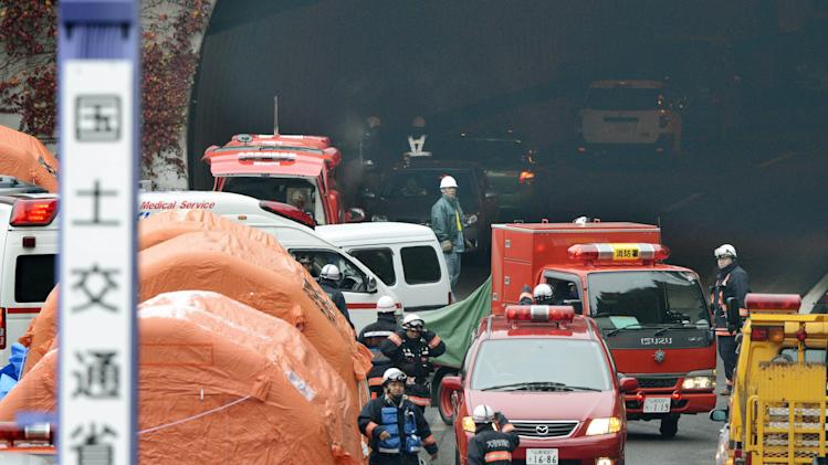 "Firefighters work at the exit of the Sasago Tunnel on the Chuo Expressway in Otsuki, Yamanashi Prefecture, central Japan, Monday morning, Dec. 3, 2012. Concrete ceiling slabs fell onto moving vehicles deep inside the tunnel Sunday, and authorities confirmed nine deaths before suspending rescue work Monday while the roof was being reinforced to prevent more collapses. The sign attached to a mobile lighting pole, left, reads ""Land and Transport Ministry."" (AP Photo/Kyodo News) JAPAN OUT, MANDATORY CREDIT, NO LICENSING IN CHINA, FRANCE, HONG KONG, JAPAN AND SOUTH KOREA"
