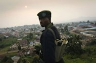 A Congolese fighter of the rebel M23 group, looks on from a hill in Bunagana, a town near the Ugandan border. Rebel fighters in the Democratic Republic of Congo seized control Sunday of more towns in the country's east, but said they would cede most of their gains to UN peacekeepers and police